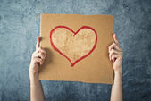 Man holding cardboard paper with heart shape drawing — Stock Photo