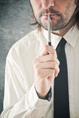 Businessman thinking with pencil in his mouth — Stock Photo