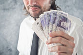 Businessman holding British pounds money — Stock Photo