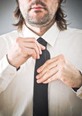 Businessman tying necktie — Stock Photo