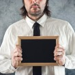 Businessman holding blank blackboard — Stock Photo