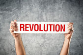 Man holding white banner with revolution title — Stock Photo