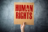 Man holding cardboard paper with HUMAN RIGHTS title — Stock Photo