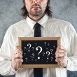 Stock Photo: Businessman holding blackboard with question marks