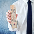 Businessman holding thermometer with temperature on Zero value — Stock Photo