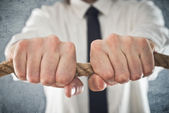 Businessman holding tight to a rope — Stock Photo