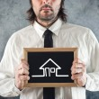Businessman holding blackboard house drawing — Photo