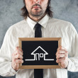 Businessman holding blackboard house drawing — Foto de Stock