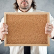 Businessman holding blank bulletin board — Stock Photo