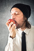Businessman eating red apple — Stock Photo