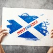 Stock Photo: SCotland Independence flag. Mholding banner with Scotish inde