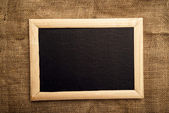 Empty blackboard on jute canvas — Stock Photo