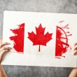 Stock Photo: Canadflag. Mholding banner with CanadiFlag.