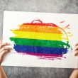 Stock Photo: LGBT flag. Mholding banner with Gay Flag.