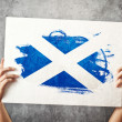 Stock Photo: Scotland flag. Mholding banner with Scotish Flag.