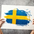 Stock Photo: Sweden flag. Mholding banner with Swedish Flag.