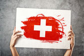 Switzerland flag. Man holding banner with Swiss Flag. — Stock Photo