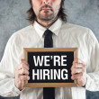 Stock Photo: Businessmholding blackboard with WE ARE HIRING title