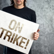 Worker on strike, man holding poster with printed protest messag — Stock Photo