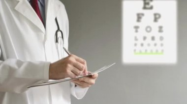 Male ophthalmologist doctor writing prescription to patient after eye examination. — Stock Video