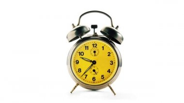 Vintage alarm clock over a white background. Time running backwards, full turn. — Stock Video