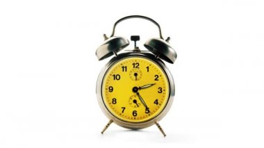 Vintage alarm clock over a white background making a twelve hours full turn — Stock Video
