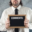 Stock Photo: Businessmholding blackboard with comments