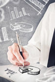 Businessman drawing pie chart and other infographics in note pad — Stock Photo