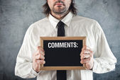 Businessman holding blackboard with comments — Stock Photo