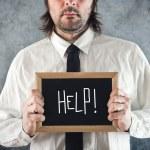 Businessman holding blackboard with HELP written — Stock Photo #41467681