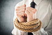 Businessman with hands tied in ropes — Stock Photo