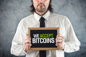 Businessman holding board with title WE ACCEPT BITCOINS — Stock Photo