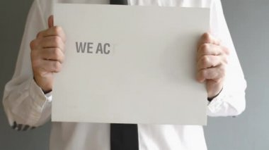 Businessman holding paper board with title WE ACCEPT BITCOINS. — Stock Video