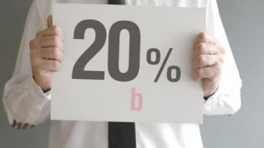 Salesman holding sale tag with twenty percent sales discount price. Consumerism concept, retail store promotion. — Stock Video