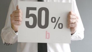 Salesman holding sale tag with fifty percent sales discount price. Consumerism concept, retail store promotion. — Stok video