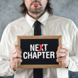 Businessmholding blackboard with NEXT CHAPTER title — Stock Photo #41899511