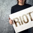 Stock Photo: RIOT. Mholding poster with printed protest message