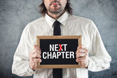 Businessman holding blackboard with NEXT CHAPTER title — Stock Photo