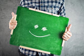 Man holding green chalkboard with smiley face — Stock Photo