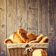 Delicious bread and rolls inwicker basket — Stock Photo