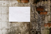 Blank white poster on grunge wall — Stock Photo