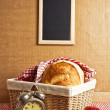Delicious bread and rolls in wicker basket — Stock Photo #42744067