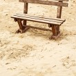 Empty wooden bench on the beach in cloudy weather — Stock Photo