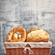 Delicious bread and rolls in wicker basket — Stock Photo