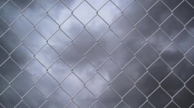 Chain link wire fence against cloudy sky time lapse — Stock Video