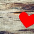 Red paper heart on grunge wooden background — Stock Photo #43129173