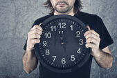 Man holding big black clock — Stock Photo