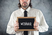 Webinar concept. Businessman holding blackboard with Webinar tit — Foto Stock