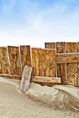 Vintage wooden fence on sandy beach — Stock Photo