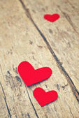 Red paper hearts on grunge wooden background — Stock Photo